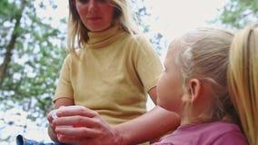Alimentaciones de la madre del primer con la niña de la cuchara contra las plantas almacen de video