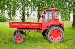 Alimentador agrícola rojo retro bajo árboles de abedul Fotografía de archivo