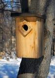 Alimentador de madeira dos pássaros na floresta do inverno Fotografia de Stock Royalty Free