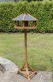 Alimentador de madera del pájaro que se coloca en un patio del jardín Foto de archivo