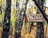 Alimentador del p?jaro con un p?jaro dentro en el bosque imágenes de archivo libres de regalías