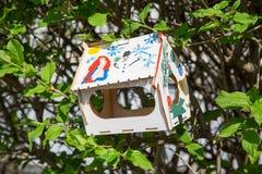 Alimentador del pájaro en el fondo de árboles verdes imagenes de archivo
