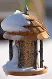 Alimentador del pájaro en nieve Fotos de archivo libres de regalías
