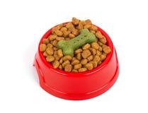 Alimentador vermelho do animal de estimação Bacia enchida com o alimento secado Kibble no fundo branco isolado Fotografia de Stock Royalty Free