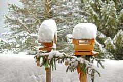 Alimentadores de madeira decorados do pássaro com sacos engrenados Imagens de Stock