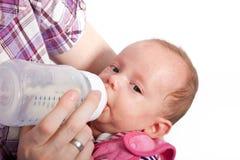 Alimentando um bebê bonito com uma garrafa do leite foto de stock royalty free