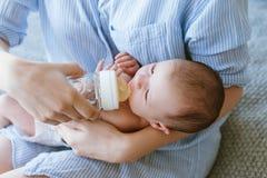 Alimentation du nouveau-né avec un mélange dans une bouteille Photo stock