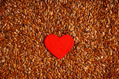 Alimentation saine. Lin oléagineux de graines de lin comme fond de nourriture et coeur rouge photos stock
