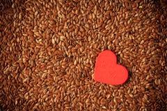 Alimentation saine. Lin oléagineux de graines de lin comme fond de nourriture et coeur rouge images libres de droits