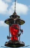 Alimentatore decorato del colibrì contro un cielo blu immagine stock