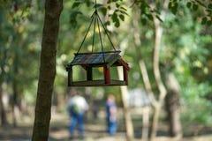 Alimentatore dell'uccello che appende nel parco di autunno fra gli alberi su fondo vago nel giorno caldo di autunno fotografia stock