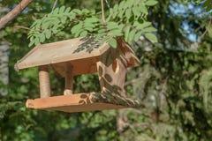 Alimentatore dell'uccello che appende su un ramo di albero immagini stock