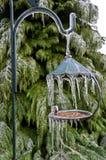 Alimentatore dell'uccello con i ghiaccioli che pendono dalla posta Immagini Stock
