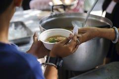 Alimentazione del povero alle mani di un mendicante Concetto di povertà immagini stock libere da diritti