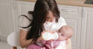 Alimentazione della donna neonata con la formula in una bottiglia stock footage