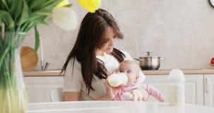 Alimentazione della madre neonata con la formula in una bottiglia stock footage