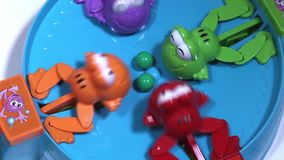 Alimentazione di quattro rane di plastica affamate con le palle colorate Gioco del bambino su velocità di raccolta delle palle stock footage