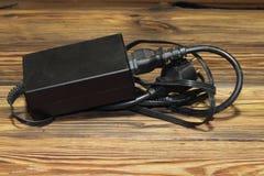 Alimentazione elettrica per le bugie del computer su una tavola di legno fotografie stock