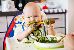 alimenter La première nourriture solide de la chéri photo stock