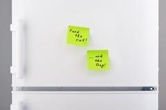 Alimentez le chat et les notes de chien sur le réfrigérateur blanc Image libre de droits