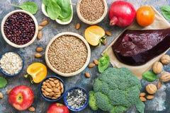Alimenti alti in ferro fegato, broccoli, cachi, mele, dadi, legumi, spinaci, melograno Vista superiore, disposizione piana immagine stock
