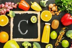 Alimenti alti in vitamina C su un fondo rustico nero di pietra Vista superiore, disposizione piana fotografia stock
