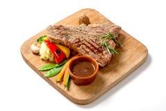 Alimenti arrostiti - bistecca di manzo del BBQ con salsa piccante e le verdure su un bordo di legno Fotografia Stock
