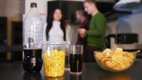 Alimenti industriali sul tavolo da cucina Chip, popcorn, soda La giovane donna viene più vicino ed eliminando la ciotola di chip stock footage