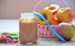 Alimenti per bambini, frutta schiacciata in un barattolo di vetro, pesca, belle pesche in un canestro, giocattolo del bambino del fotografia stock