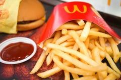 Alimenti a rapida preparazione del ` di McDonalds con le fritture della patata e l'hamburger del formaggio Fotografie Stock