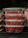 Alimenti sani al mercato: Semi rossi del melograno da vendere Quattro pacchetti impilati nel profilo fotografie stock libere da diritti
