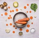 Alimenti sani, cucinare e concetto vegetariano carote affettate con spinaci e le spezie, presentati intorno ai vasi d'annata cuci Fotografie Stock Libere da Diritti