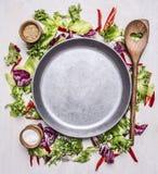 Alimenti sani, cucinare e lattuga vegetariana di concetto con un cucchiaio, un sale e un pepe di legno, presentati intorno al pos Fotografia Stock