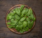 Alimenti sani, cucinare ed ingredienti vegetariani di concetto per l'insalata, leaveson fresco degli spinaci un tagliere di legno Immagini Stock
