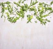Alimenti sani, cucinare ed insalata vegetariana della rucola di concetto sulla fine rustica di legno di vista superiore del fondo Immagini Stock