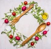 Alimenti sani, cucinare ed insalata vegetariana di concetto con i pomodori ciliegia, ravanelli, cucchiaio di legno delle spezie e Fotografie Stock