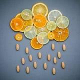 Alimenti sani e concetto della medicina Pillole di vitamina C e del citru Immagine Stock