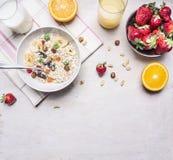Alimenti sani, nocciole vegetariane di concetto, fragole ed arance, farina d'avena, confine del succo del latte, posto per testo  Fotografie Stock