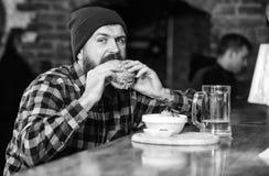 Alimento alto da caloria Conceito delicioso do hamburguer Aprecie o gosto do hamburguer fresco O homem com fome do moderno come o imagens de stock royalty free