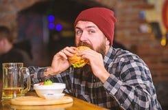 Alimento alto da caloria Refei??o da fraude Conceito delicioso do hamburguer Aprecie o gosto do hamburguer fresco O homem com fom fotos de stock