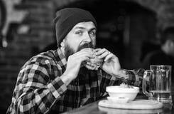Alimento alto da caloria Refei??o da fraude Conceito delicioso do hamburguer Aprecie o gosto do hamburguer fresco O homem com fom imagens de stock royalty free