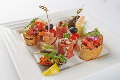 Alimento appetitoso gastronomico sul piatto quadrato Fotografia Stock