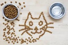Alimento asciutto per i gatti Due ciotole Superficie di legno Forma del gatto Immagini Stock Libere da Diritti
