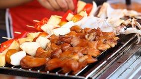 Alimento asiático de la calle Bbq, parrilla en los palillos Alimentos de preparación rápida en países asiáticos almacen de metraje de vídeo