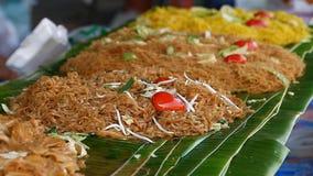 Alimento asiático de la calle Tallarines de arroz frito tradicionales y plato popular en Asia almacen de metraje de vídeo