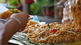 Alimento asiático de la calle Tallarines de arroz frito tradicionales y plato popular en Asia almacen de video