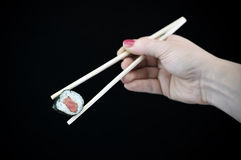 Alimento asiático del sushi de los pescados sin procesar en palillos imagenes de archivo