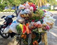 Alimento asiatico tradizionale della via in Bali - la motocicletta è appesa con i pacchetti con differenti spuntini fotografia stock