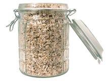 Alimento: Avena sin procesar en un tarro de cristal (aislado) Imagen de archivo