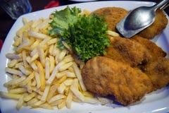 Alimento Batatas fritas e carne ou peixes panados com as folhas frescas verdes da salada Tempo de jantar Almoço no restaurante Ne imagem de stock